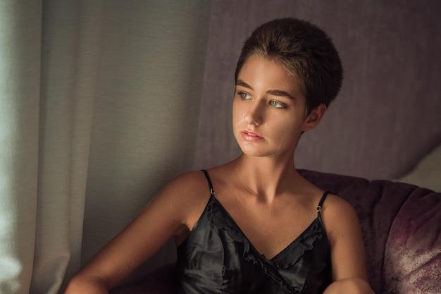 Linda mujer joven sentada en una silla de pelo corto y triste