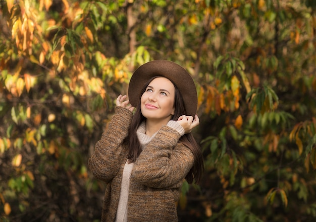 Una linda mujer joven con un sombrero marrón posa en un parque de otoño