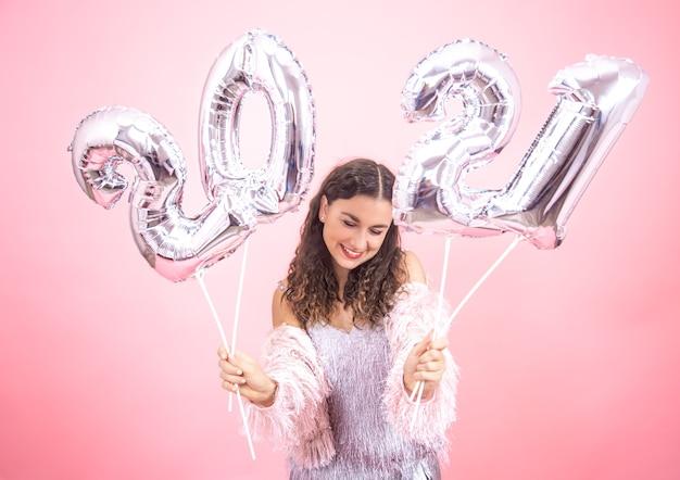 Linda mujer joven con una sonrisa en un traje festivo, sosteniendo globos plateados para el concepto de año nuevo