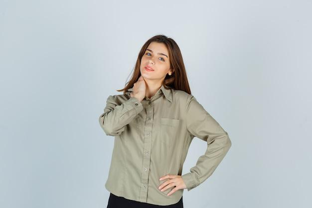 Linda mujer joven sosteniendo la mano en el cuello en camisa, falda y mirando alegre, vista frontal.