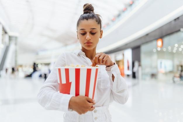 Linda mujer joven sosteniendo palomitas de maíz en el centro comercial