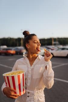 Linda mujer joven sosteniendo palomitas de maíz en un estacionamiento del centro comercial