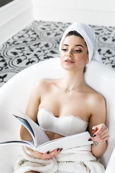 Linda mujer joven con una toalla sobre su cabeza se sienta en el baño y lee una revista