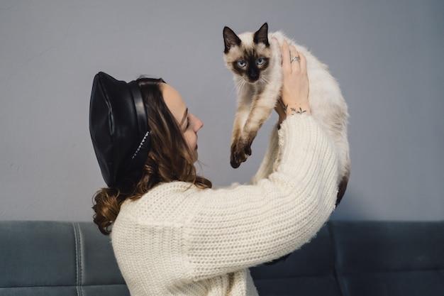 Linda mujer jugando con gato siamés