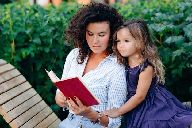 Linda mujer lee un libro a su amada hija