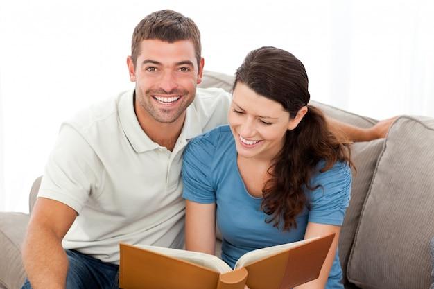 Linda mujer leyendo un libro con su novio en el sofá