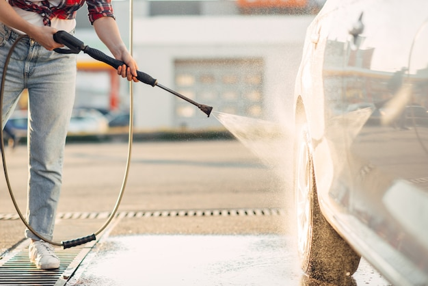 Linda mujer limpia las ruedas del coche con pistola de agua