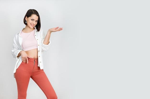 Linda mujer morena de 30 años en coral jeans camiseta rosa sin mangas y camisa blanca sobre fondo blanco.
