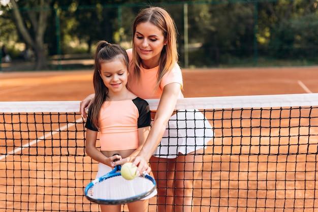 Una linda mujer le muestra a su hija cómo golpear la pelota con una raqueta