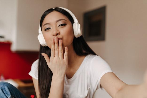 Linda mujer de ojos marrones en auriculares grandes hace selfie y sopla beso