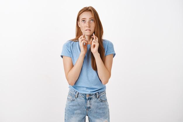 Linda mujer pelirroja espera que dios escuche las oraciones mordiéndose el labio inferior mientras está de pie sobre una pared gris cruzando los dedos para tener buena suerte mientras desea aprobar los exámenes y entrar en la famosa universidad