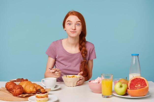 Linda mujer pelirroja con una trenza se sienta en una mesa, desayuna, con entusiasmo come copos de maíz con leche