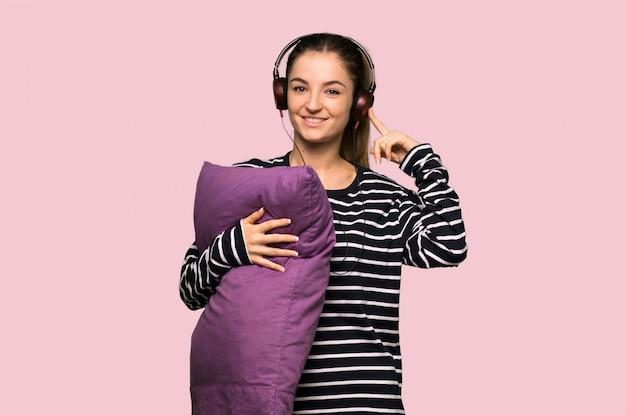 Linda mujer en pijama escuchando música con auriculares en pared rosa aislado