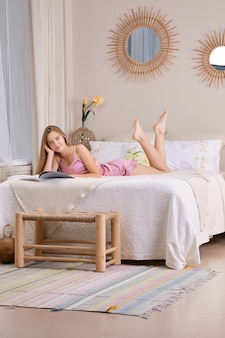 Linda mujer en pijama de seda en la cama hojeando una revista