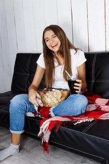 Linda mujer riendo, viendo la televisión, sentado en el sofá en casa.