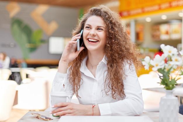 Linda mujer rizada sonriente disfruta de una conversación telefónica con su mejor amigo