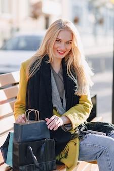 Linda mujer rubia atractiva feliz con paquetes en la calle en un clima cálido y soleado