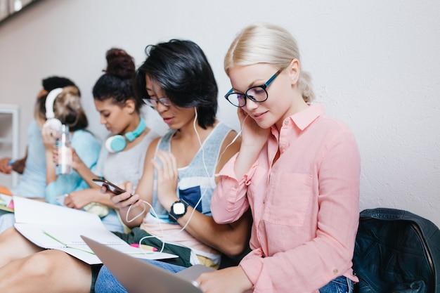 Linda mujer rubia en blusa rosa sosteniendo portátil y escuchando música en auriculares con un amigo morena con gafas. retrato interior de elegantes estudiantes internacionales relajándose en auriculares.