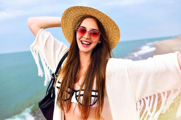 Linda mujer rubia haciendo selfie en la playa del océano, vestida con traje boho y gafas de sol divertidas, sombrero de paja vintage, enviando un beso.