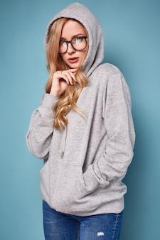 Linda mujer rubia positiva en gris con capucha y gafas