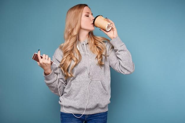 Linda mujer rubia positiva en sudadera con capucha con teléfono y café
