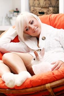 Linda mujer rubia sentada en la silla con conejito