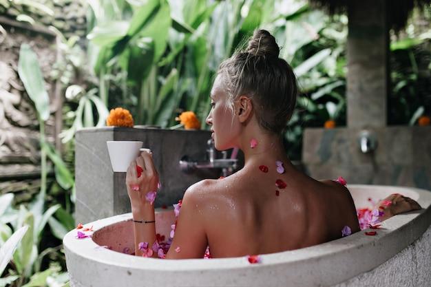 Linda mujer rubia tomando café por la mañana y acostado en el baño.