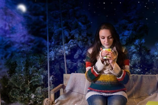 Linda mujer sentada en un columpio con una manta y sosteniendo una taza con bebida caliente en un parque cubierto de nieve por la noche con abetos, vistiendo suéter de lana cálido y bufanda de punto