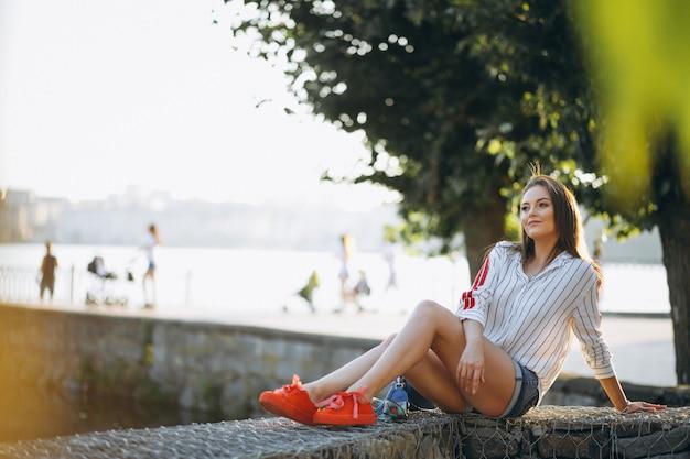 Linda mujer sentada junto al lago