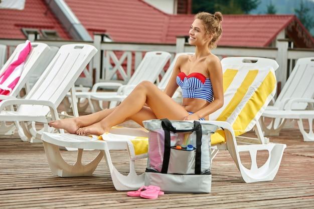 Linda mujer sentada en la silla de playa, en la orilla de la piscina.