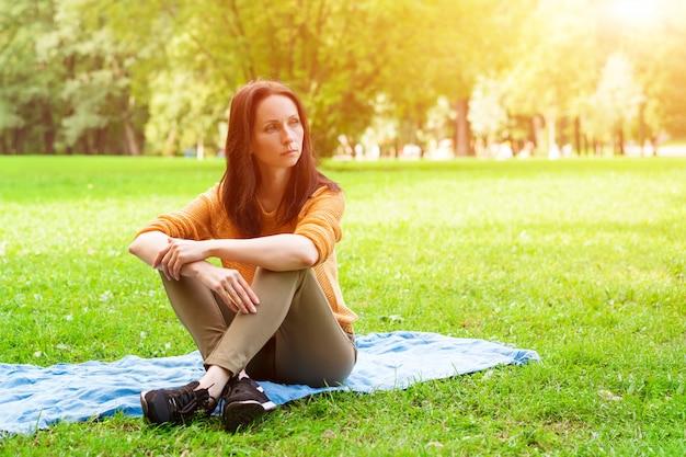 Linda mujer sentada sobre una estera en el césped del parque, descansando