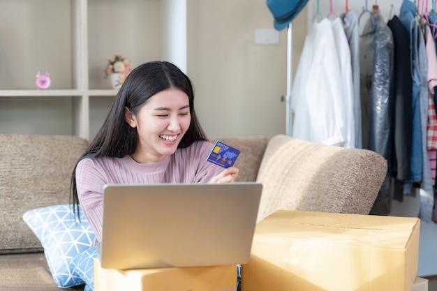 Linda mujer sonriendo y mirando a la tarjeta de crédito en la mano