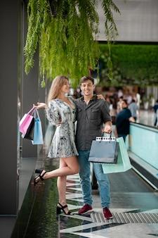 Linda mujer sonriente posando en un abrazo con un hombre joven con una camisa gris y jeans. compras