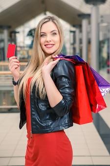 Linda mujer sosteniendo bolsas de compras y mostrando la tarjeta de crédito en blanco