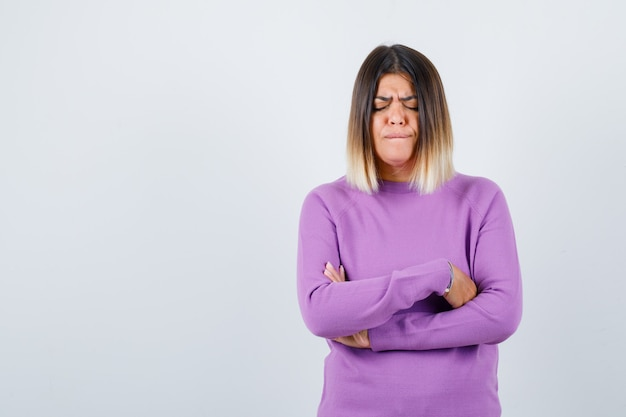 Linda mujer sosteniendo los brazos cruzados en suéter morado y mirando triste. vista frontal.