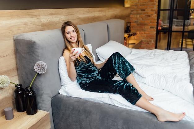 Linda mujer con taza de café en el apartamento de lujo moderno
