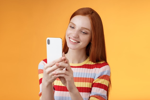 Linda mujer tierna joven pelirroja glamour chica sosteniendo teléfono inteligente tomando fotos vibraciones urbanas de verano blogger femenina disparando historia en línea de pie felizmente fondo naranja sonriendo.