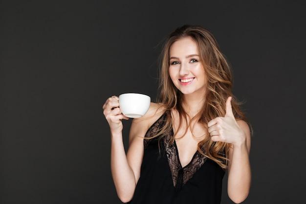Linda mujer tomando café y hacer gesto de pulgares arriba