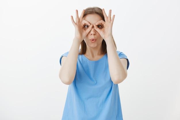 Linda mujer tonta mirando a través de gafas de mano, gestos bien