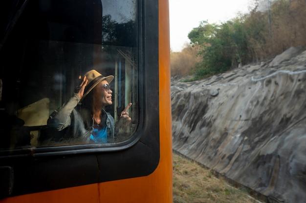 Linda mujer turista sonriendo y buscando viajar en tren de verano
