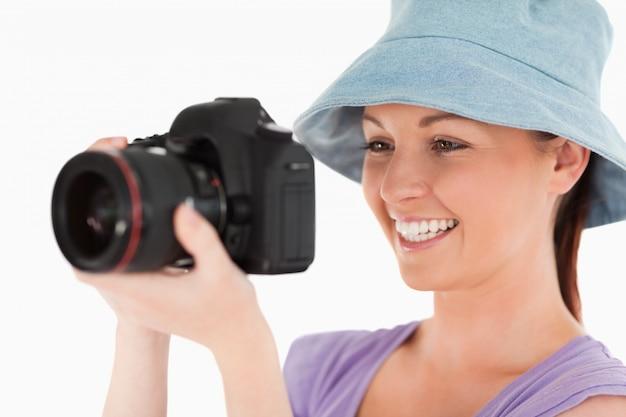 Linda mujer usando una cámara mientras está de pie