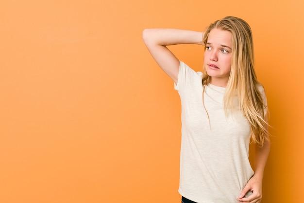 Linda y natural adolescente mujer tocando la parte posterior de la cabeza, pensando y haciendo una elección.