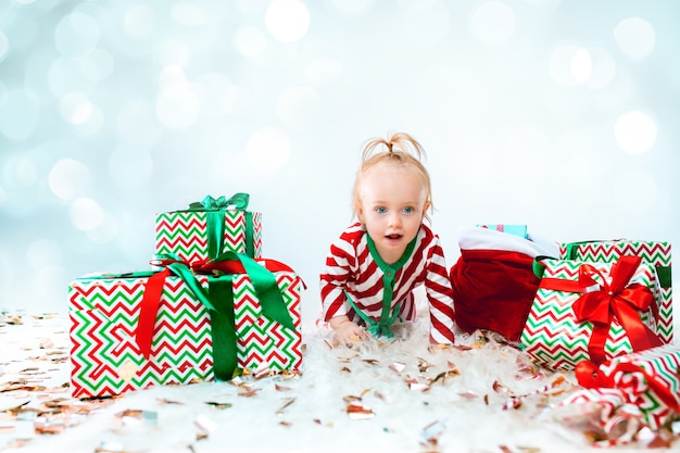 Linda niña de 1 año cerca de gorro de papá noel sentado en el piso con bola de navidad