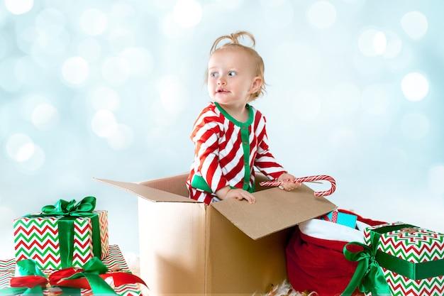 Linda niña de 1 año sentado en caja durante navidad