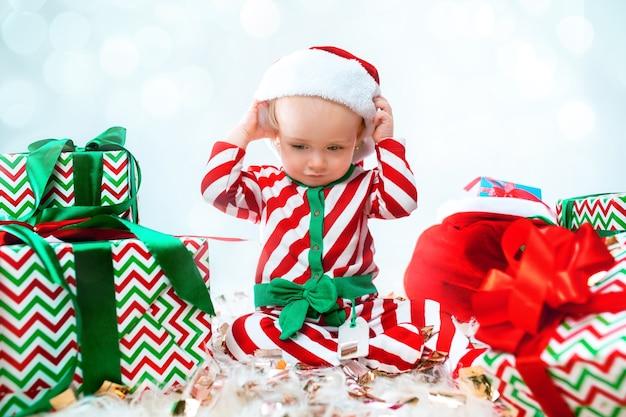Linda niña de 1 año vistiendo gorro de papá noel posando sobre adornos navideños