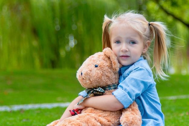 Linda niña de 3 años sosteniendo un oso de peluche al aire libre
