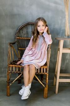 Linda niña de 5-6 años con elegante vestido rosa sentado en la silla de madera pared gris. fiesta de cumpleaños. celebracion.