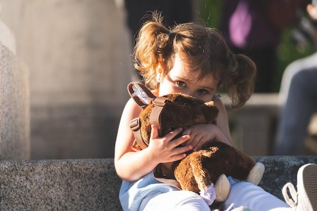 Linda niña abrazando el mono de peluche al aire libre