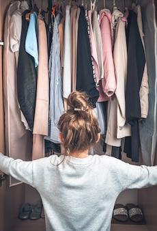 Linda niña abrió el armario. vista lateral.