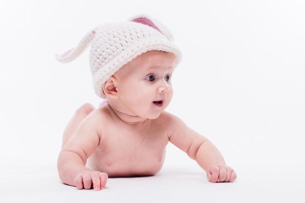 Linda niña acostada desnuda en una pared blanca con un sombrero